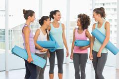 Fit smiling young women with exercise mats Stock Photos
