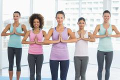 Fit class with hands joined at fitness studio - stock photo