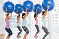 Fit women holding blue fitness balls in exercise room - stock photo