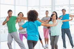 Fitness class and instructor doing pilates exercise - stock photo