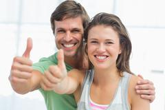 Portrait of a fit young couple gesturing thumbs up - stock photo
