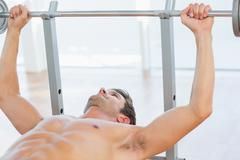 Stock Photo of Shirtless fit man lifting the barbell bench press