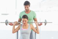 Trainer helping fit woman to lift barbell bench press - stock photo