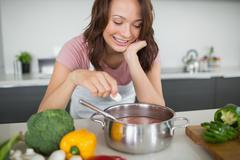 Stock Photo of Smiling woman preparing food in kitchen
