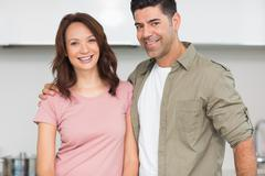 Portrait of a smiling couple in the kitchen - stock photo
