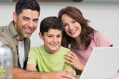 Smiling couple with son using laptop Stock Photos