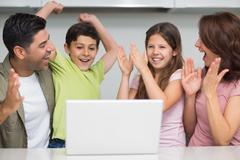 Stock Photo of Cheerful couple with kids using laptop