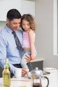 Stock Photo of Well dressed father carrying his daughter while preparing food