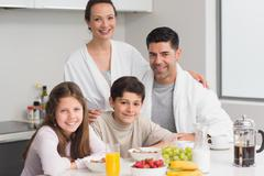 Stock Photo of Portrait of happy kids enjoying breakfast with parents