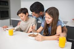 Stock Photo of Happy young kids enjoying breakfast with father