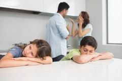 Sad young kids while parents quarreling in kitchen - stock photo