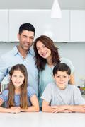 Portrait of a happy family of four in kitchen Stock Photos