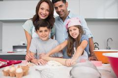 Portrait of a family of four preparing cookies in kitchen Stock Photos