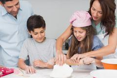 Family of four preparing cookies in the kitchen Stock Photos
