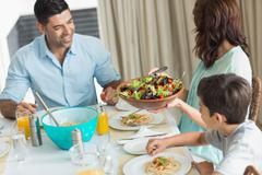 Stock Photo of Happy family of three sitting at dining table