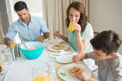 Stock Photo of Family of three sitting at dining table