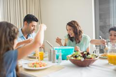 Family of four at dining table in the home Stock Photos
