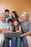Stock Photo of Extended family using laptop on sofa in living room