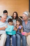 Stock Photo of Extended family sitting on sofa with gift boxes in living room