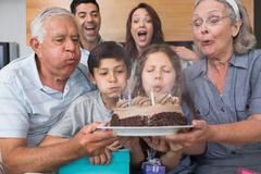 Stock Photo of Extended family blowing candles on cake in living room