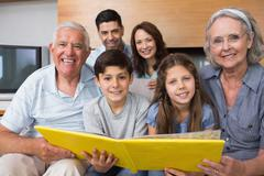 Stock Photo of Portrait of an extended family looking at their album photo