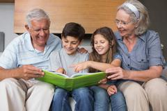 Happy grandparents and grandkids looking at album photo - stock photo
