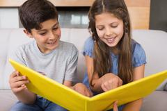 Stock Photo of Smiling siblings looking at photo album in living room