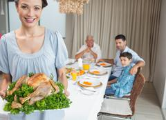 Woman holding chicken roast with family at dining table Stock Photos