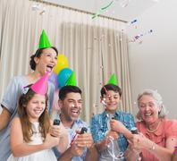 Cheerful extended family playing with Christmas crackers Stock Photos