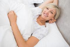 Pretty mature woman resting in bed - stock photo