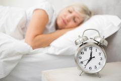 Stock Photo of Woman sleeping in bed with alarm clock in foreground at bedroom