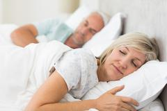 Mature couple sleeping with eyes closed in the bed - stock photo