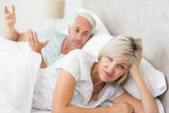 Portrait of a woman besides man in bed Stock Photos