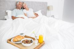 Stock Photo of Couple sitting on bed with breakfast in foreground