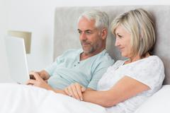 Stock Photo of Concentrated couple using digital tablet in bed