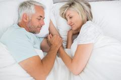 Mature couple lying in bed at home Stock Photos