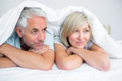 Closeup of a mature couple lying in bed - stock photo