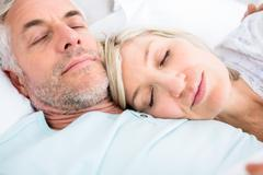 Loving mature couple sleeping in bed Stock Photos