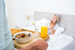 Stock Photo of Woman sitting in bed with breakfast in foreground