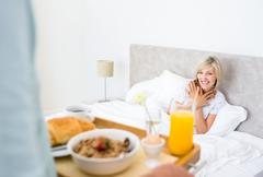 Stock Photo of Happy woman sitting in bed with breakfast in foreground