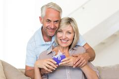 Smiling mature man surprising woman with a gift on sofa - stock photo