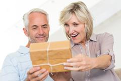 Smiling woman surprising mature man with a gift on sofa - stock photo