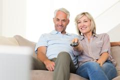 Happy couple watching tv on sofa - stock photo