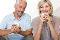 Stock Photo of Smiling mature couple with coffee cups sitting on sofa