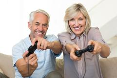 Cheerful mature couple playing video game on sofa - stock photo