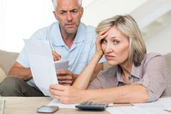 Tensed mature couple with bills at home Stock Photos