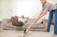 Man resting on couch while woman vacuuming area rug Stock Photos