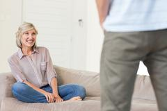 Smiling woman looking at man in living room - stock photo