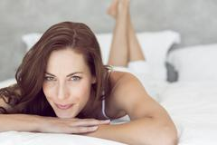 Stock Photo of Closeup of a pretty smiling woman lying in bed