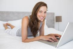 Relaxed young woman using laptop in bed - stock photo